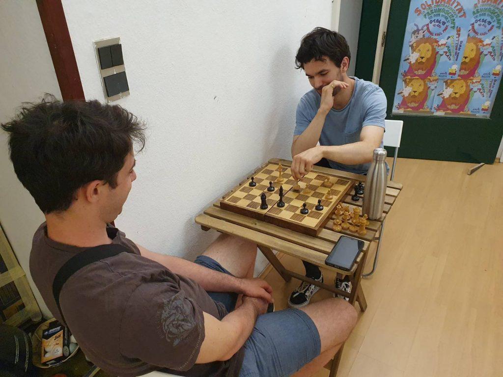 2 Menschen spielen Schach, eine Person macht einen Zug